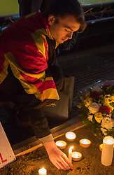 Trafalgar Square, London, March 24th 2016. A man places a candle in front of a giant Belgian flag as people gather in London's Trafalgar Square to light candles and lay flowers in memory of those who lost their lives in the Brussels terror attacks on March 22nd in which 31 people were killed and dozens injured.