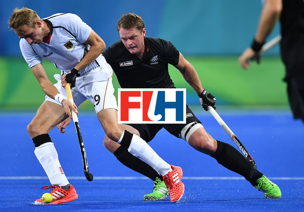 Germany's Niklas Wellen (L) vies with New Zealand's Bradley Shaw during the men's quarterfinal field hockey Germany vs New Zealand match of the Rio 2016 Olympics Games at the Olympic Hockey Centre in Rio de Janeiro on August 14, 2016. / AFP / MANAN VATSYAYANA        (Photo credit should read MANAN VATSYAYANA/AFP/Getty Images)