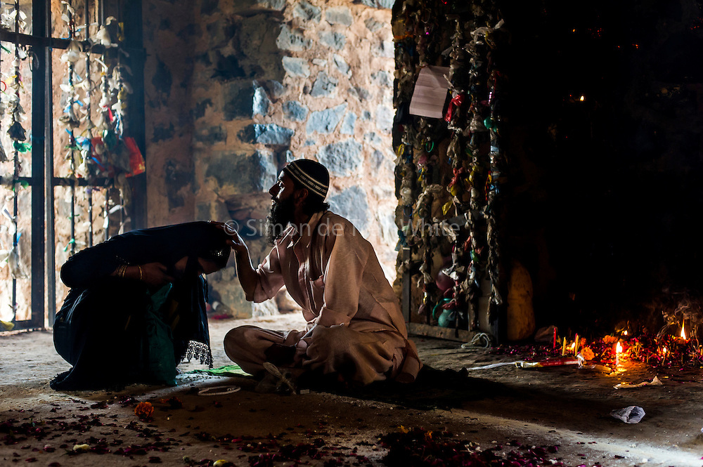 19th March 2015, New Delhi, India. A Sufi 'pir' (master) performs a cleansing rite on a female supplicant in the ruins of Feroz Shah Kotla in New Delhi, India on the 19th March 2015<br /> <br /> PHOTOGRAPH BY AND COPYRIGHT OF SIMON DE TREY-WHITE a photographer in delhi<br /> + 91 98103 99809. Email: simon@simondetreywhite.com<br /> <br /> The13th century fortress-city of Firoz Shah Kotla in Delhi is thronged weekly with thousands of supplicants seeking favour from supernatural beings of smokeless fire, - Djinns. These magical entities also known as Jinn, Jann or Genies spring from Islamic mythology as well as pre-Islamic Arabian mythology. They are mentioned frequently in the Quran and other Islamic texts and inhabit an unseen world called Djinnestan. Believers, mostly Muslim but from other faiths too, circumnavigate the ruins clutching dozens of photocopied requests, flower petals, incense, and candles. They visit the numerous niches and alcoves in the catacombs said to be occupied by different djinns and greet and salute the invisible occupants with offerings.  A copy of their requests, often with detailed contact information, photographs and even police reports to bolster the case is left with the &lsquo;Baba&rsquo; before moving on to the next where the procedure is repeated - like making applications at different departments of a bureaucracy.