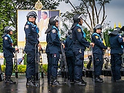 23 NOVEMBER 2012 - BANGKOK, THAILAND:  Thai riot police stand under a portrait of Bhumibol Adulyadej, the King of Thailand, during preparations for large anti-government protests scheduled to take place in Bangkok. Thai authorities have imposed the Internal Security Act (ISA), that enables police to call on the army if needed to keep order, and placed thousands of riot police in the streets around Government House in anticipation of a large anti-government protest Saturday. The group sponsoring the protest, Pitak Siam, said up to 500,000 people could turn out to protest against the government. They are protesting against corruption in the current government and the government's unwillingness to arrest or pursue fugitive former Prime Minister Thaksin Shinawatra, deposed in 2006 coup and later convicted on corruption charges. The current Thai Prime Minister is Yingluck Shinawatra, Thaksin's sister.      PHOTO BY JACK KURTZ