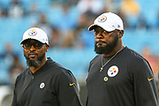 Pittsburgh Steelers head coach Mike Tomlin and player engagement coordinator Terry Cousin waking out to the field during a NFL football game against the Carolina Panthers, Thursday, Aug. 29, 2019, in Charlotte, N.C. The Panthers defeated the Steelers 25-19.  (Brian Villanueva/Image of Sport)