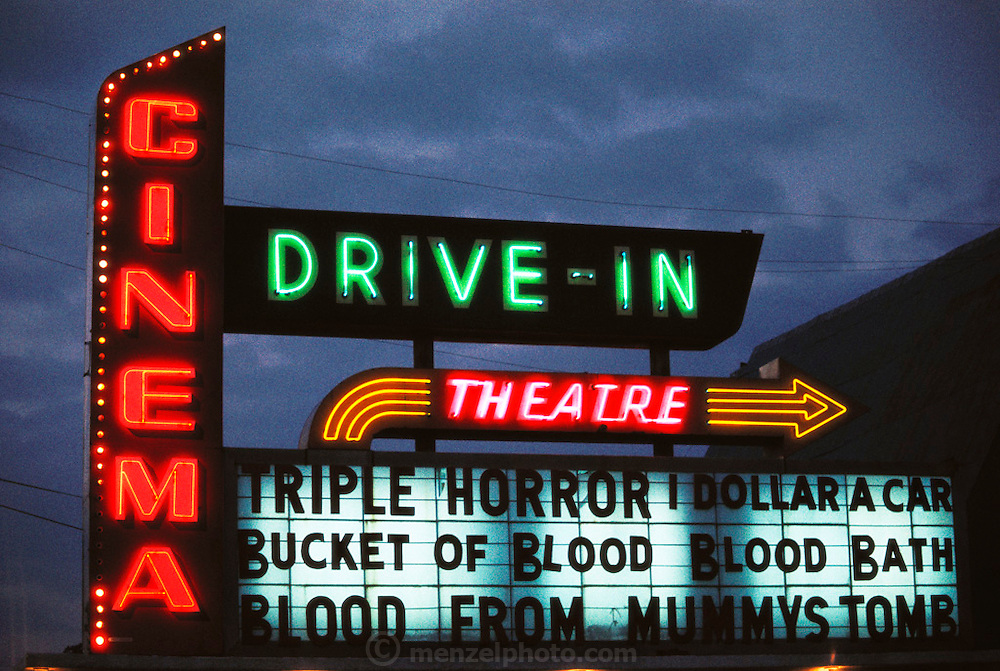 Illuminated drive-in movie theater sign at dusk. Triple Horror: Bucket of Blood, Blood Bath, Blood from Mummy's Tomb. One dollar a car entry fee. USA.