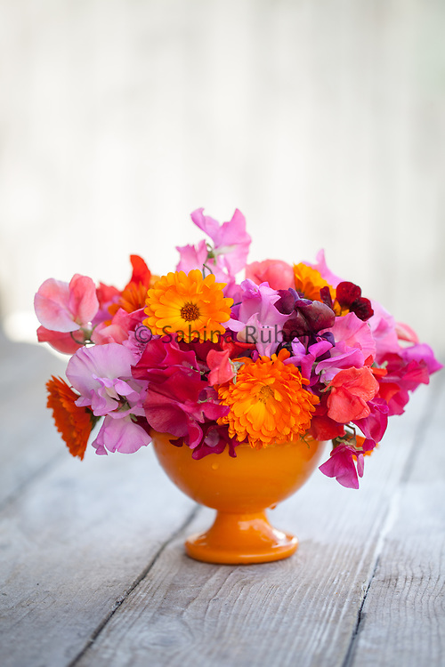 Bright flower arrangement with pink and red sweet peas and calendula in orange vase