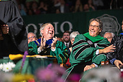 President M. Duane Nellis and Dave Scholl react to speach by honorary degree recipient  Robert Kirshner at Graduate Commencement. Photo by Ben Siegel