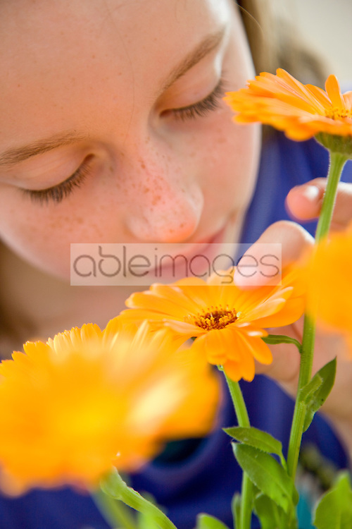 Young Girl Holding and Smelling Orange Flowers