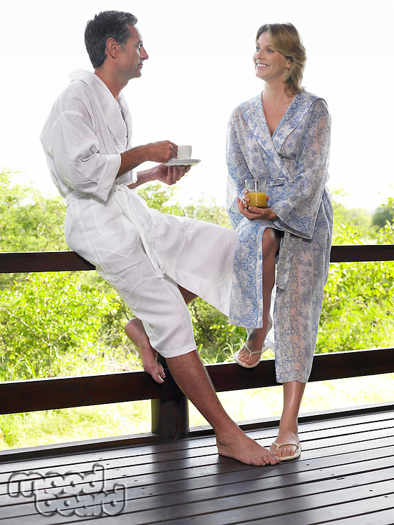 Adult man and woman in bathrobes leaning on terrace railing holding cups