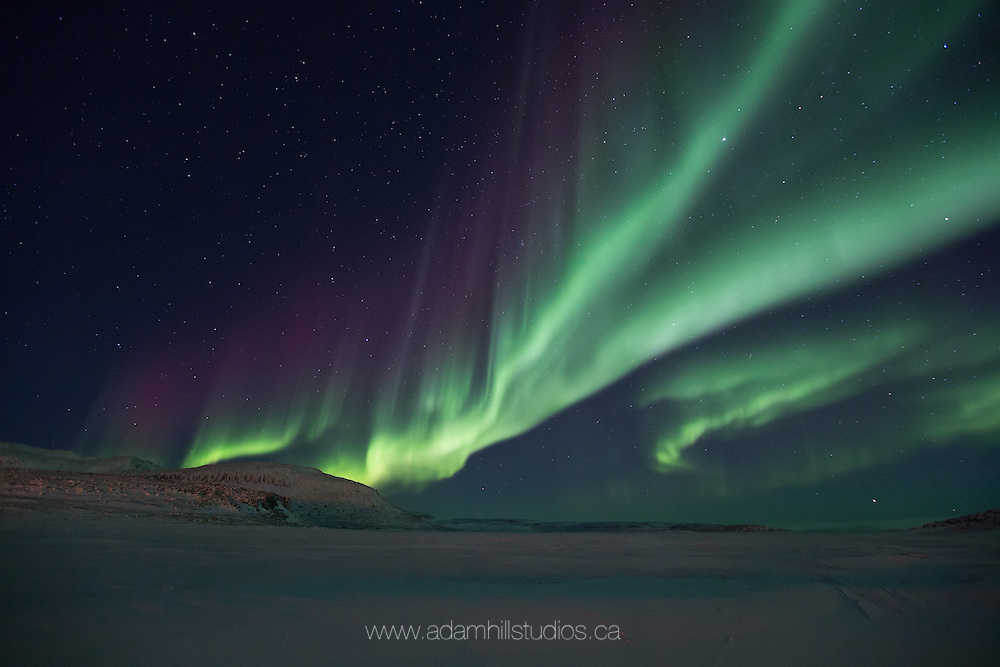 The Aurora Borealis start to flow over King's Bay in Ulukhaktok high in Canada's Arctic.