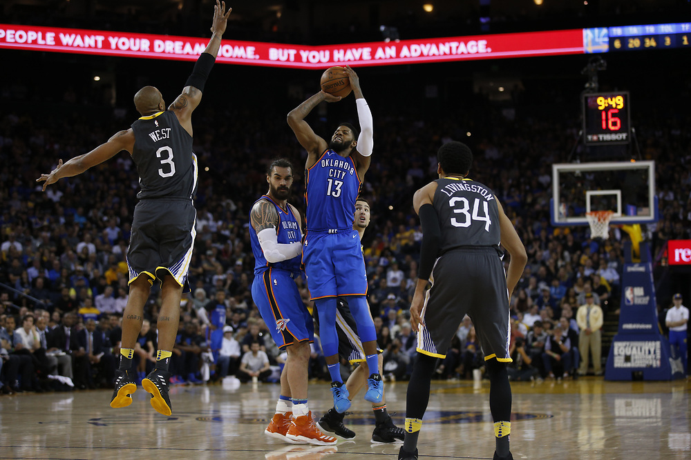 Oklahoma City Thunder forward Paul George (13) takes a shot against Golden State Warriors forward David West (3) during the second half of an NBA game between the Warriors and Oklahoma City Thunder at Oracle Arena, Tuesday, Feb. 6, 2018, in Oakland, Calif. The Warriors lost 105-125.