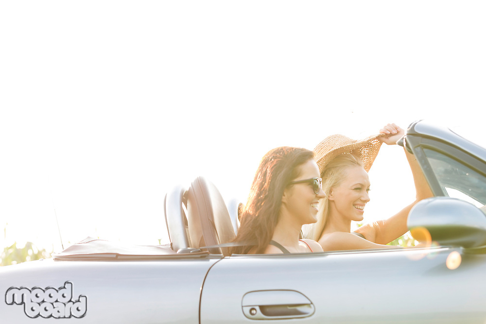 Happy female friends enjoying road trip in convertible against clear sky