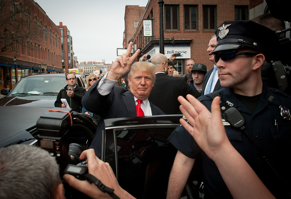 Donald Trump flashes the peace sign and waves to the crowd as he leaves Portsmouth, NH in his Limo. Real Estate Mogul, TV Star and Presidential hopeful Donald Trump makes a visit to Portsmouth, NH for meetings and a meet and greet as he walks around Downtown Portsmouth.