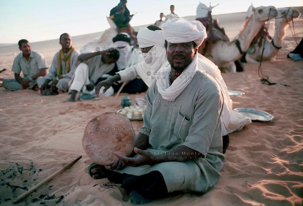 Libia, Ghadhames 2002.Tuareg con il pane cotto nel deserto del Sahara.Libya, Ghadhames 2002.Tuareg with bread baked in the Sahara .