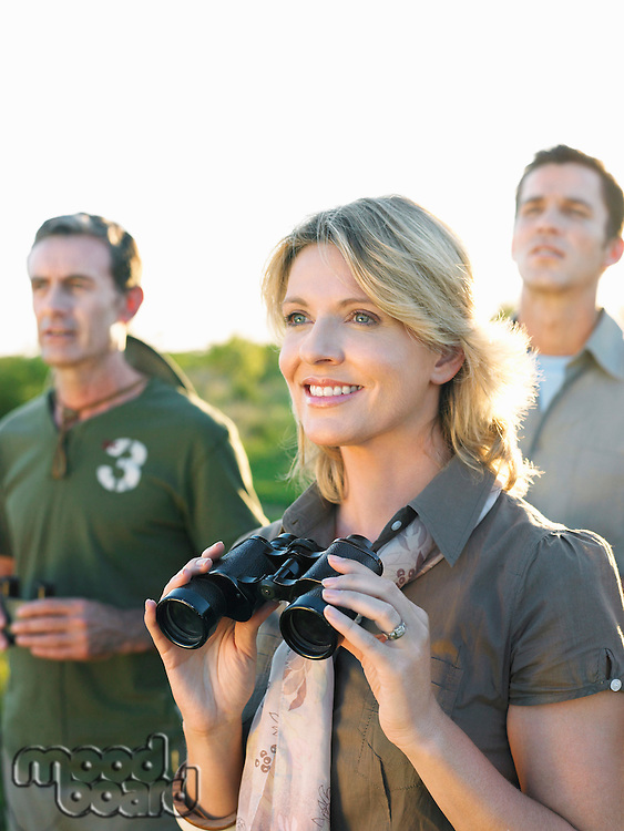 Two men and woman looking at view woman holding binoculars
