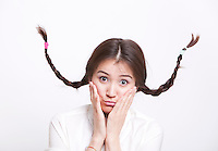 Portrait of confused young woman with braids curling upwards against white background