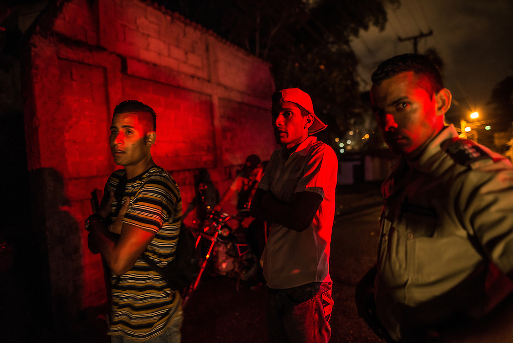 CARRIZAL, VENEZUELA - DECEMBER 9, 2016:  Young men watch as police officers arrest their friend, while on patrol in a slum in Carrizal, Venezuela. A severe economic crisis in Venezuela, caused by the drop in oil prices and years of economic mismanagement under a Socialist government, has lead to an alarming rise in crime and insecurity in the country.  Hyperinflation has left both the working class and professional class of workers with salaries that cannot purchase enough food to feed their families. Many people are turning to crime to make ends meet.  PHOTO: Meridith Kohut for The New York Times