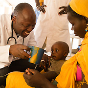Dr Benoit Mbiya of Médecins Sans Frontières (MSF) helping a severely dehydrated Roki Walet Tadousmane at the MSF health centre at the Mbera camp for Malian refugees in Mauritania on 2 March 2013.