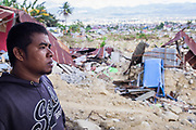 Portrait of Ronald (32) in front of his Father's (Sabudin) car repair shop who was killed  when he a sinkhole swallowed the Balaroa Village after a 7.5 earthquake magnitude hit off the coast of Donggala, Palu Sulawesi Central, Indonesia on Sept. 28th causing a tsunami.  Ronald was able to save 6 other family members including his mother, 2 sister in law, 1 younger sister, 1 older brother and 2 nephews. <br /> <br /> Sabudin owns a car repair shop for many decades<br /> <br /> <br /> Residents fear as much as 70 per cent of the population there has been killed. The rural village &mdash; a few kilometres outside Palu &mdash; was home to about 2,000 people until Friday.  Search and rescue workers using earth-moving equipment have toiled for days to find survivors.  But more than 1,000 people are still missing,