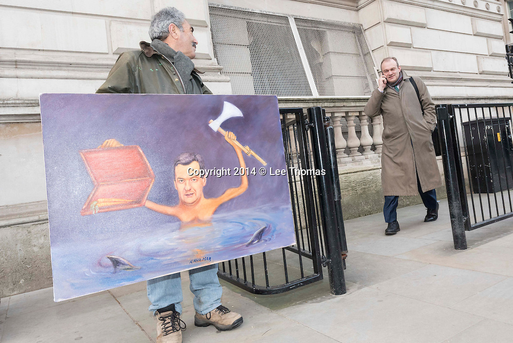 Downing Street, London, UK. 3rd December, 2014. Political Artist, Kaya Mar, displays his new painting of George Osborne as ministers leave Downing Street on the day the Chancellor is due to deliver his Autumn Statement in the House of Commons. Pictured:  Ed Davey.