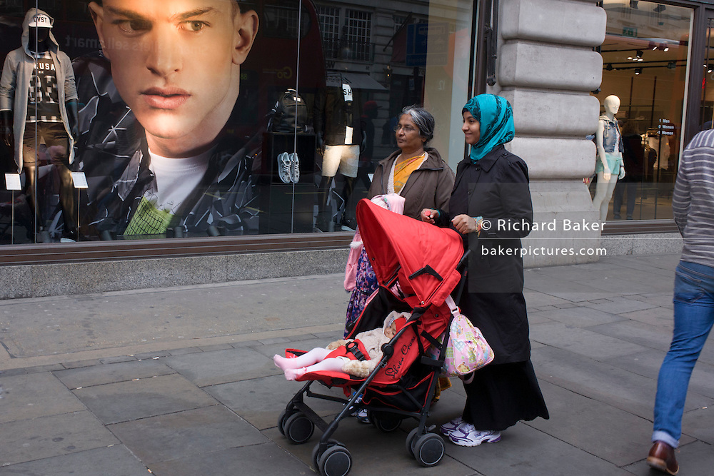 Muslin family and a large image of a male model in the window of clothing retailer H&M on Regents Street, London borough of Westminster.