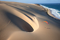 paraglider soars over remote dunes on the island of Bazaruto, Mozambique