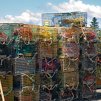 A stack of colorful lobster traps piled up on a dock in Port Clyde, Maine on a fine summer day with a bright blue sky and white, fluffy clouds.
