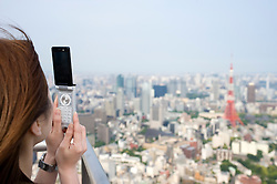 Tourist photographing Tokyo Tower and skyline of Tokyo with a camera phone