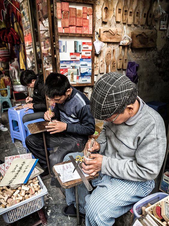 Men design stamps in a shop along Hang Quat street in Hanoi's Old Quarter, Vietnam, Southeast Asia