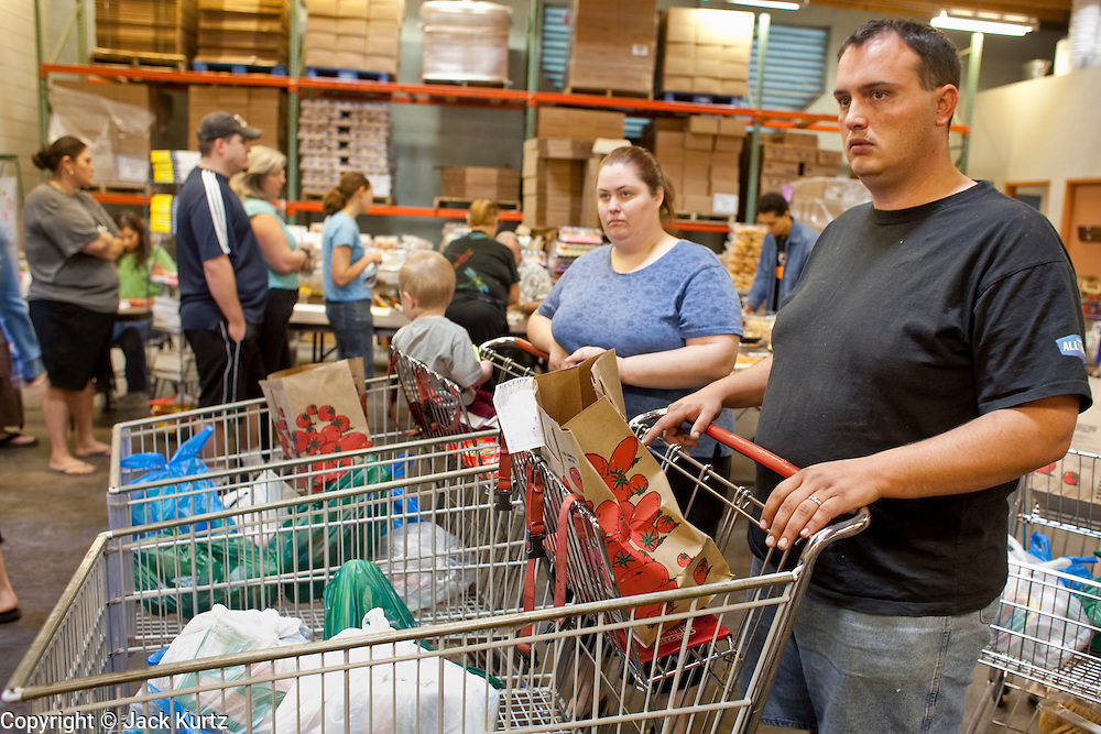 Apr. 3, 2009 -- MESA, AZ:  KATRINA HALL, lher husband, TIM HALL and their son, ZANE HALL, from Tempe, AZ, go through the line at the United Food Bank in Mesa, AZ. Hall said he drives a tourist bus but as the tourism and leisure industry has suffered in the recession his work in disappearing and in March he only work five days. A spokesperson for the United Food Bank in Mesa, AZ, said demand has increased by more than 100 percent in the last year. She said that at this time in 2008, about 175 people a week (the food bank is open one day a week) bought 200 boxes a food but now they were seeing about 350 people per week and they were buying 400-450 boxes of food per week. Each box of food cost $16 and contains enough food for five meals for two people, including meat, fruit and vegetables and starches. In addition to the food boxes, the food bank gives away perishables, like fresh baked goods and produce, that are donated by Phoenix area grocery stores and food producers. She said the number of donations to the food bank have increased as the economy has worsened but each donation is smaller and the gap between donations and what the food bank needs is widening.    Photo by Jack Kurtz / ZUMA Press