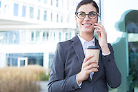Happy businesswoman using cell phone while holding disposable cup outdoors
