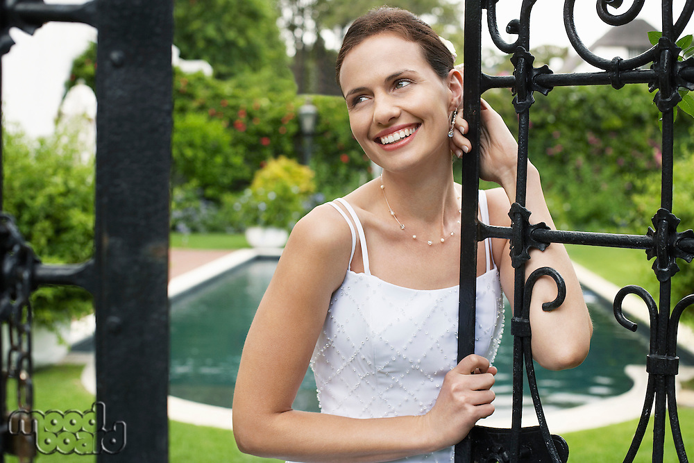 Mid adult bride leaning on gate looking away portrait