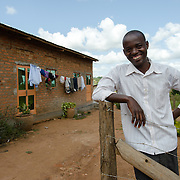 Joseph Gabula, pictured in front of his home, works as a driver at Afripads, a social enterprise that manufactures reusable sanitary pads in the village of Kitengeesa in the Central Region of Uganda. Gabula's wife, Irene Nakayima is the Production Manager at Afripads, and through their income from the comapany they were able to acquire a piece of land and build their home. Irene was also able to complete a diploma in Social Administration.