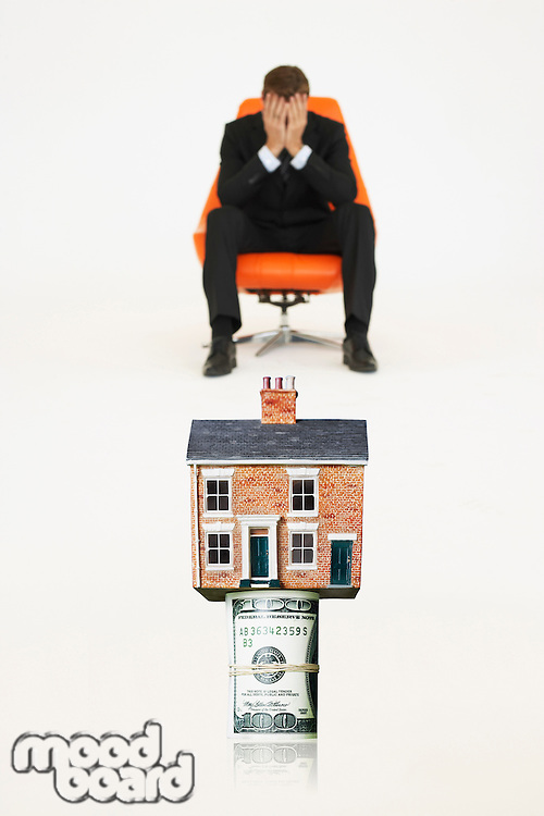 House on top of roll of bills with worried businessman on chair representing expensive real estate