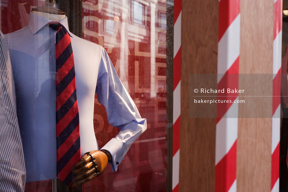 Businessman style of shirt and striped tie worn by mens' clothing shop mannequin in city window, with matching stripes.