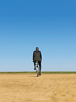 Businessman riding bicycle in desert back view