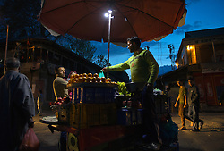 A vendor sells fruit in a night market in Baramulla, Kashmir.