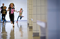 JEROME A. POLLOS/Press..Makenzee Thompson, 6, runs down the hallway with her classmates at Mullan Trail Elementary during the Mighty Moose March fundraiser Tuesday. Students raised fund by collecting pledges for each lap they completed. The funds will be used for classroom materials and instructional aides that will help maintain programs at the Post Falls school despite budget cuts.