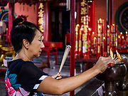 13 JULY 2017 - BANGKOK, THAILAND: A woman lights incense at Chao Mae Thapthim Shrine in the Dusit district of Bangkok. The Chinese shrine is at the foot of Krung Thon Bridge and serves poor communities along the Chao Phraya River. The shrine is along a part of the riverfront the government wants to tear down to build an esplanade. The future of the shrine itself is unknown, but many of the communities around it could be evicted and razed.        PHOTO BY JACK KURTZ