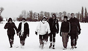 Group of male and female teenagers on a snowy day at London park. London, Greenford, UK, 1981.
