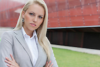 Close-up portrait of confident businesswoman against office building