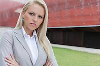 Close-up portrait of confident businesswoman against office building