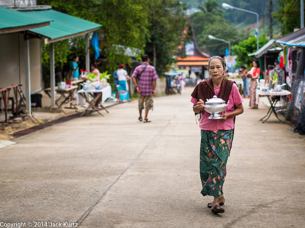 16 SEPTEMBER 2014 - SANGKHLA BURI, KANCHANABURI, THAILAND: A woman walks up the road to make merit and present Mon Buddhist monks with food during the morning alms round in the Mon community in Sangkhla Buri. The Mon were some of the first people to settle in Southeast Asia, and were responsible for the spread of Theravada Buddhism in Thailand and  Indochina. The Mon homeland is in southwestern Thailand and southeastern Myanmar (Burma). The Mon in Thailand traditionally allied themselves with the Thais during the frequent wars between Burmese and Siamese Empires in the 16th - 19th centuries and the Mon in Thailand have been assimilated into Thai culture. The Mon in Myanmar were persecuted by the Burmese government and many fled to Thailand. Sangkhla Buri is the center of Burmese Mon culture in Thailand because thousands of Mon came to this part of Thailand during the persecution.    PHOTO BY JACK KURTZ