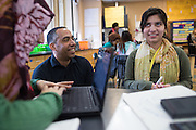 Science teacher Corey Skinner helps Fatima Ahmad, left, and Urmila Biswa during class at Rochester International Academy in Rochester, New York on Tuesday, February 23, 2016. The district is in the early stages of a planned 1:1 device to student program.