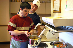 Man with learning disability cooks his own meal in a sheltered housing scheme with help from support worker; UK