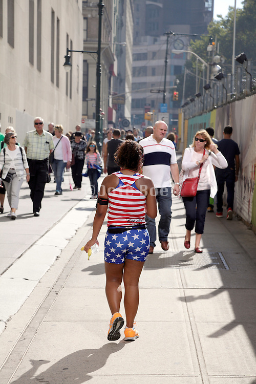 woman walking in American flag clothing Down Town Manhattan by the World Trade construction site