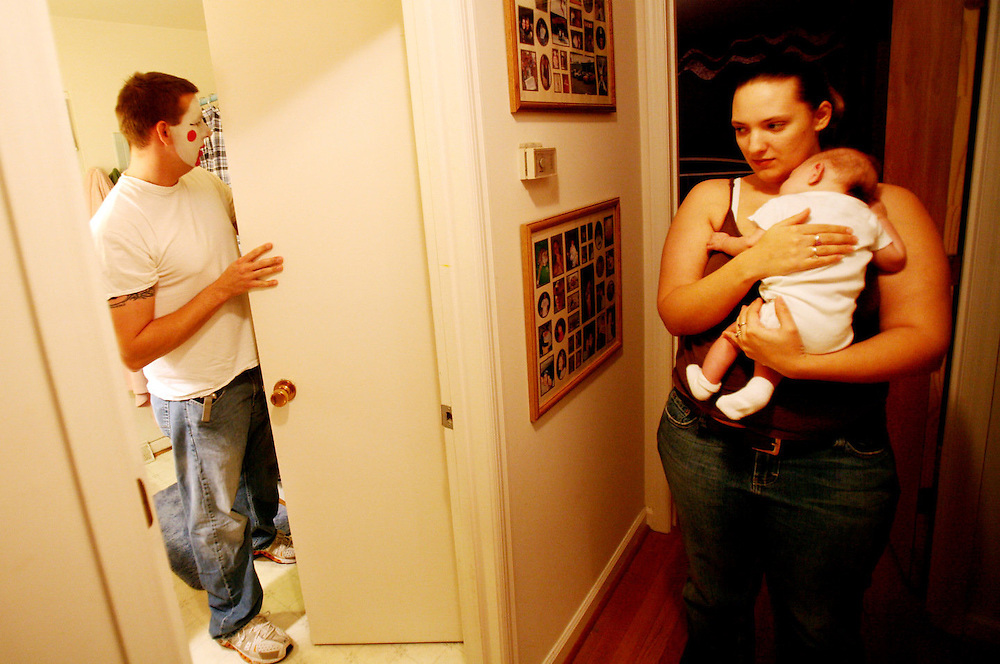 """Wife, Sheena, and son, Zander wait for Aaron L. Clark to take off his makeup after his night job as a clown at Applebee's restaurant. Aaron works full-time and freelance, often seven days a week, as """"Ziggy The Clown"""" to help pay for his son, Zander's medical bills. Zander was born with was born August 17th, 2006 with Hypoplastic Left Heart Syndrome, and had heart surgery the first day he was born. Zander is scheduled for his second open heart surgery in January."""