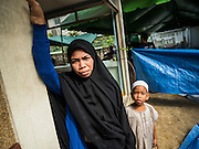 24 SEPTEMBER 2015 - BANGKOK, THAILAND:   A Muslim woman and her child watch the sacrifice of sheep during the celebration of Eid al-Adha at Haroon Mosque in Bangkok. Eid al-Adha is also called the Feast of Sacrifice, the Greater Eid or Baqar-Eid. It is the second of two religious holidays celebrated by Muslims worldwide each year. It honors the willingness of Abraham to sacrifice his son, as an act of submission to God's command. Goats, sheep and cows are sacrificed in a ritualistic manner after services in the mosque. The meat from the sacrificed animal is supposed to be divided into three parts. The family retains one third of the share; another third is given to relatives, friends and neighbors; and the remaining third is given to the poor and needy.   PHOTO BY JACK KURTZ