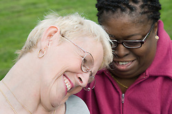 Woman with Cerebral Palsy sharing a joke with her carer,