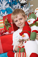 Boy (5-6) holding stuffed snowman in front of Christmas tree, portrait