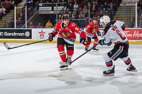 KELOWNA, BC - FEBRUARY 7: Trevor Wong #8 of the Kelowna Rockets passes the puck as Matthew Quigley #5 of the Portland Winterhawks tries to block the pass during first period at Prospera Place on February 7, 2020 in Kelowna, Canada. (Photo by Marissa Baecker/Shoot the Breeze)