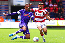 Carlton Morris of Rotherham United slides in to tackle Jon Taylor of Doncaster Rovers - Mandatory by-line: Ryan Crockett/JMP - 07/09/2019 - FOOTBALL - The Keepmoat Stadium - Doncaster, England - Doncaster Rovers v Rotherham United - Sky Bet League One