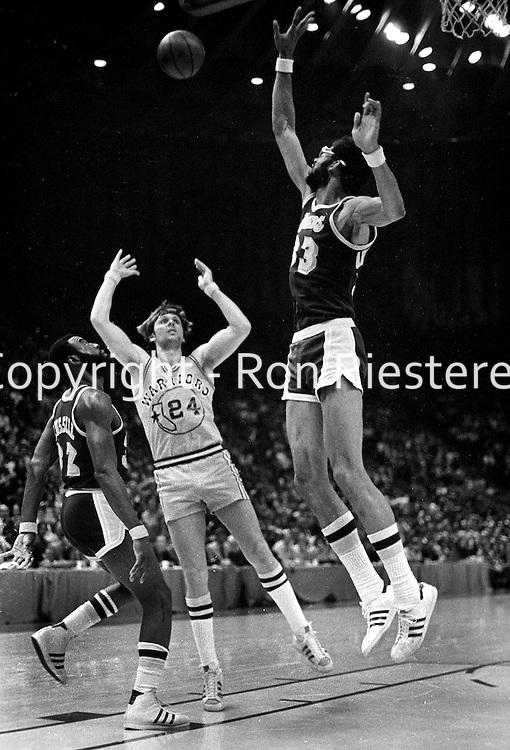 Warriors Rick Barry trys to shoot over Kareem Abdul-Jabbar..Warriors vs Lakers 1977. (photo/<br /> Ron Riesterer)